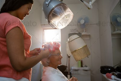 Side view of beautician adjusting curlers on senior woman hair