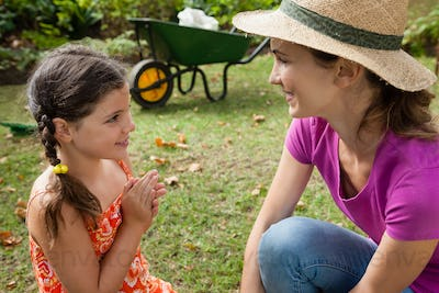 Smiling mother and daughter talking on field