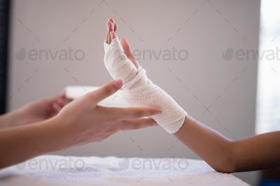 Close-up of female therapist wrapping bandage on hand