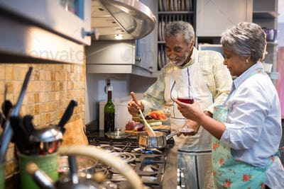 Senior couple preparing food in kitchen