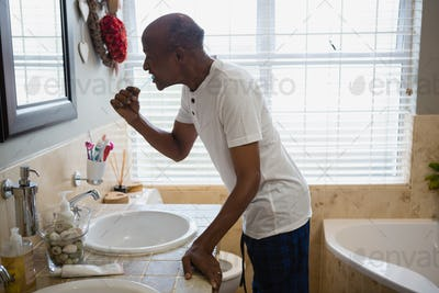 Senior man brushing teeth by sink in bathroom