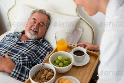 Cropped hand of female doctor serving food to senior patient relaxing on bed