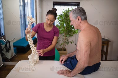 Female therapist explaining shirtless senior male patient with artificial spine