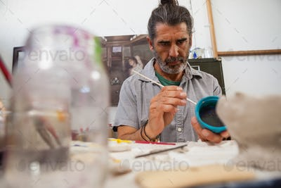 Attentive man painting bowl
