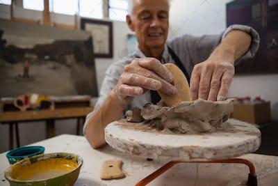 Attentive senior man molding clay