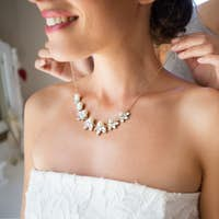 Midsection of bridesmaid fastening bride necklace in room