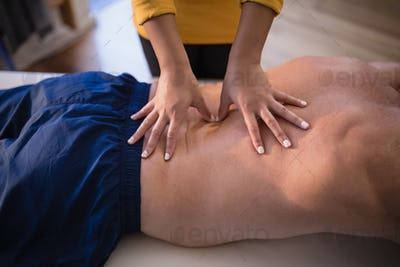 Midsection of female therapist giving back massage to shirtless male patient
