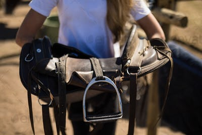 Girl holding horse saddle in the ranch