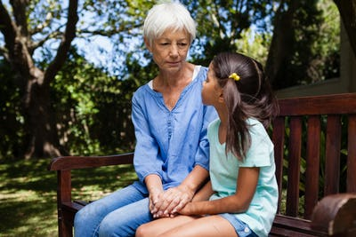 Grandmother and granddaughter holding hands while sitting on bench