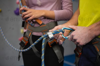 Midsection of athletes adjusting safety harness in club
