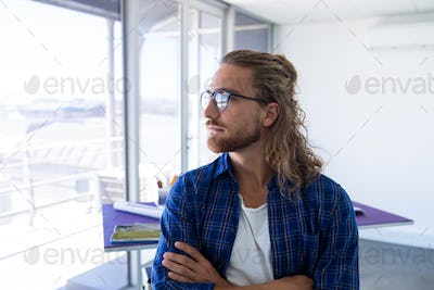 Male architect standing with arms crossed in office