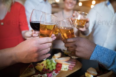 Close-up of friends toasting drinks