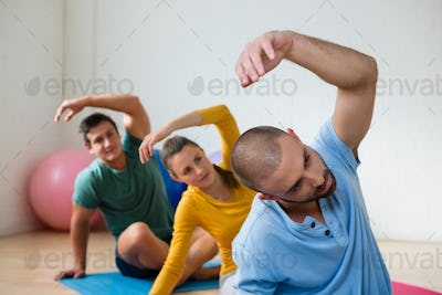 Yoga teacher with student exercising in club
