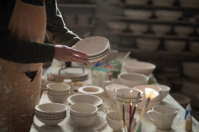 Mid section of male potter holding bowls