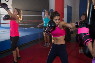 Young female boxers practicing boxing by ring