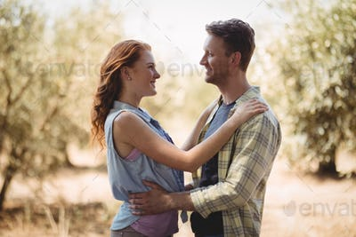 Happy young couple looking at each other while standing at olive farm
