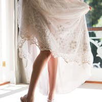 Low section of bride in wedding dress and sandals standing at home
