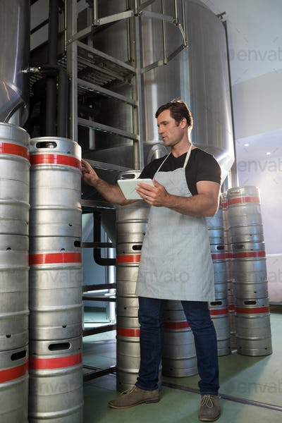 Full length of worker counting kegs at warehouse