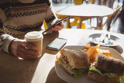 Mid section of man with breakfast using tablet in cafe