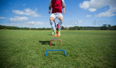 Soccer players practicing on obstacle