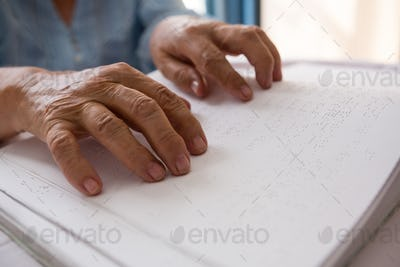Hands of senior woman reading braille in nursing home
