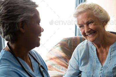 Nurse talking to senior patient in nursing home