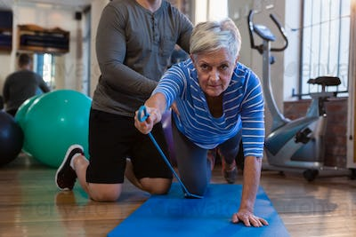 Physiotherapist assisting senior woman in performing exercise with resistance band