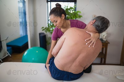 Young female therapist examining buttocks of shirtless senior male patient sitting on bed
