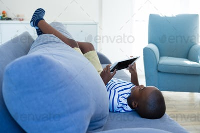 Boy using tablet computer while lying by cushion on sofa at home