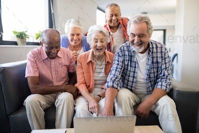 Cheerful senior friends looking at laptop on table