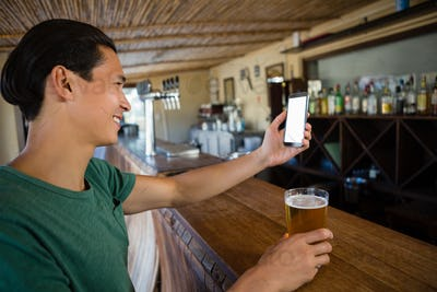 Smiling man taking selfie while having beer at bar