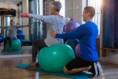 Physiotherapist assisting senior woman on exercise ball and dumbbells