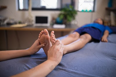 Boy lying on bed while receiving foot massage from female therapist