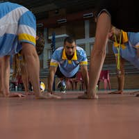 Volleyball players doing push-ups with coach