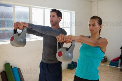 Confident athletes lifting kettlebells
