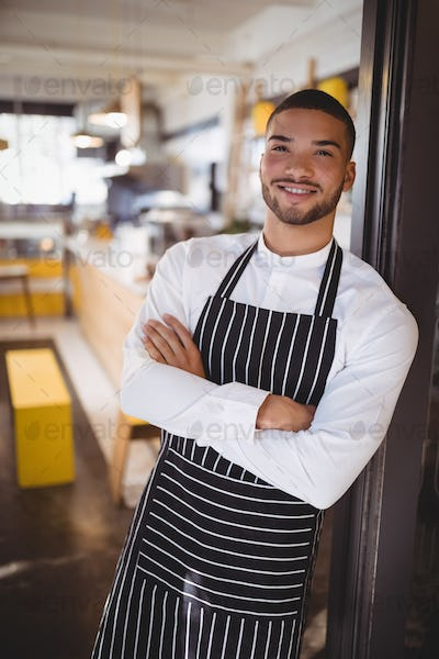Portrait of handsome young waiter standing with arms crossed
