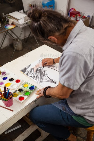 Man sketching at table