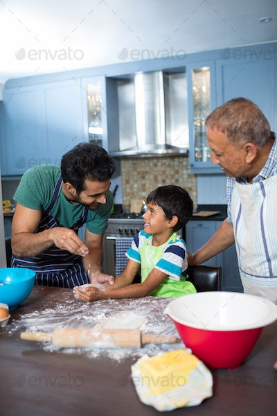 Happy father sprinkling flour on son hand while preparing food with grandfather