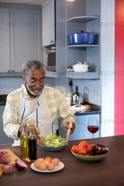Senior man making salad while sitting in kitchen