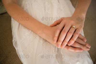 Midsection of bride wearing wedding ring while sitting on sofa