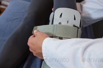 Physiotherapist tying leg pad