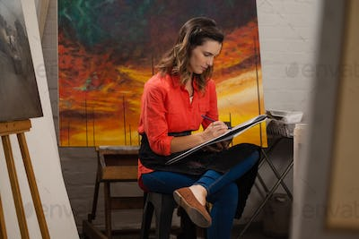 Woman painting in drawing book