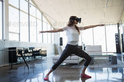 Businesswoman wearing virtual reality simulator exercising in office