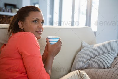 Woman having coffee in the living room at home