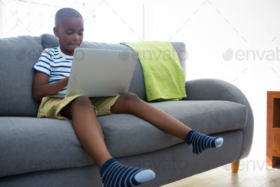 Boy using laptop while sitting on sofa at home