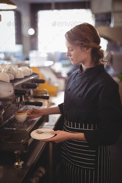 Young waitress making coffee from espresso maker