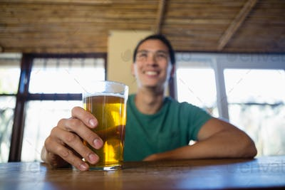 Happy man with beer glass looking away