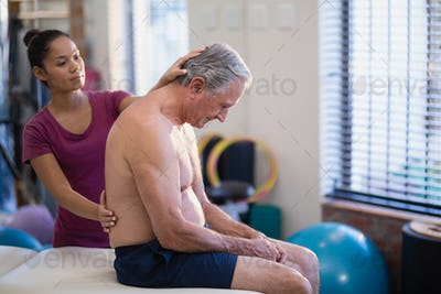Young female therapist giving back massage to senior male patient sitting on bed