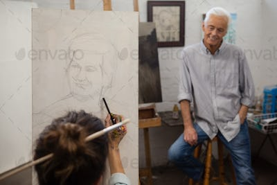 Senior man watching while artist drawing on canvas