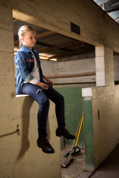 Girl sitting in stable